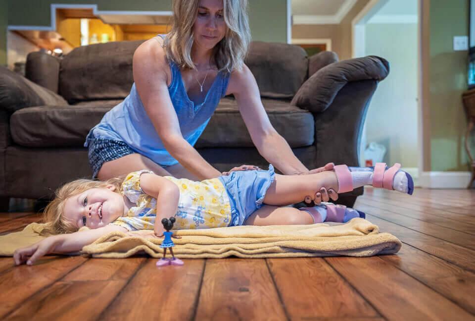 Adalyne, who has SMA Type 1, stretching with her mom