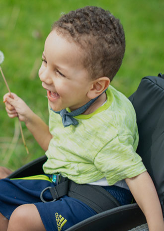 Malachi, who has SMA Type 1, laughing while he holds a dandelion